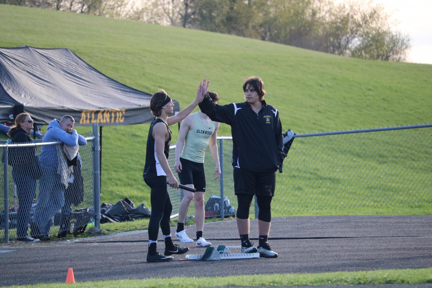 GIMME FIVE - Junior Cale Roller gives sophomore Joe Weaver a good-luck high five before he competes in his race. Roller can often be seen on the throwing field, while Weaver competes in various hurdle events.