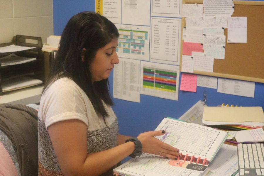 Alyssa Dovenspike consults her planner inside her office. She is excited to be a counselor for high school students.