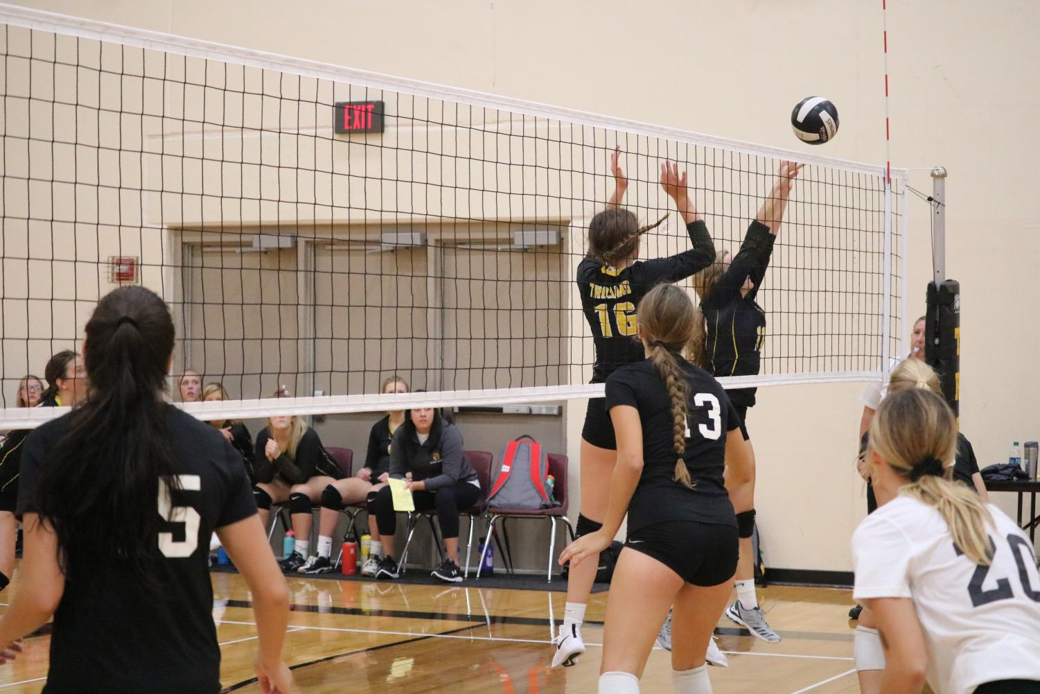 Junior Caroline Pellett sends the ball over the net while freshman Aubrey Guyer comes in for backup. The two girls combined for 13 kills on Tuesday night.