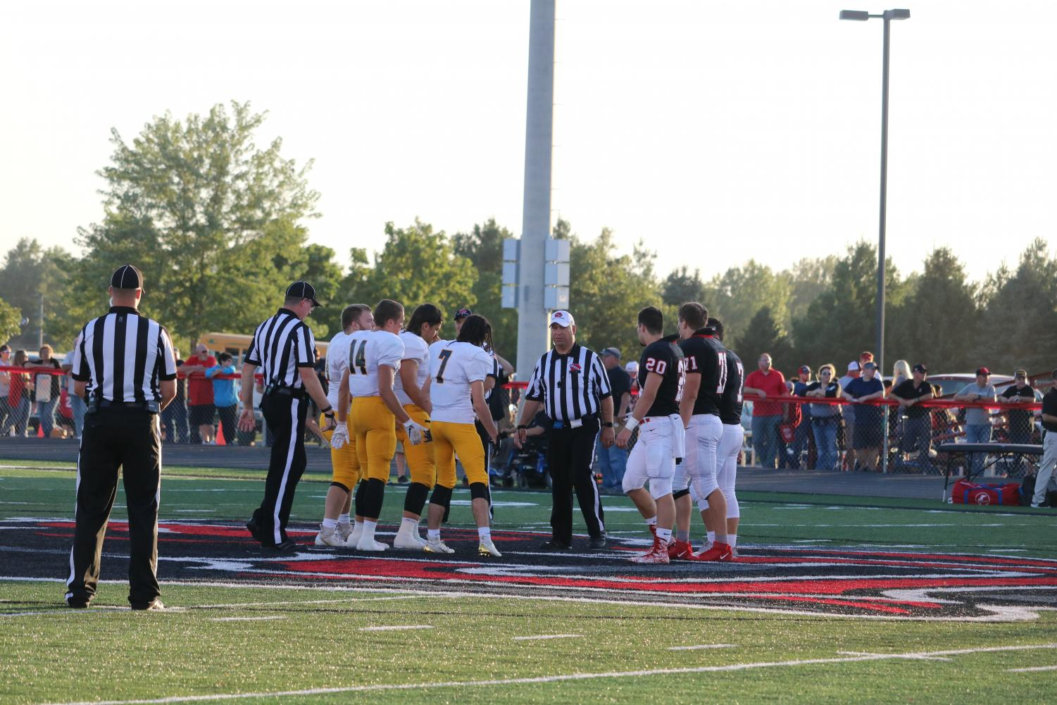 The 2019 football captains head to midfield for the coin toss against Creston. The captains are seniors Sage Archibald, Cale Roller, and Tyler Moen, and junior Colin Mullenix.