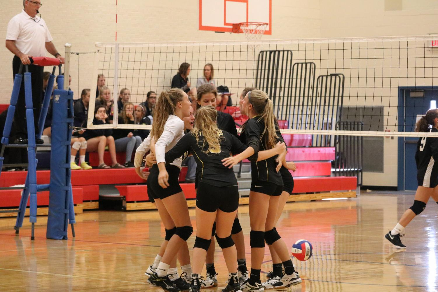 The Trojan volleyball team cheers one another on at a competition last season. The girls came in second in the ACGC quad on Tuesday.