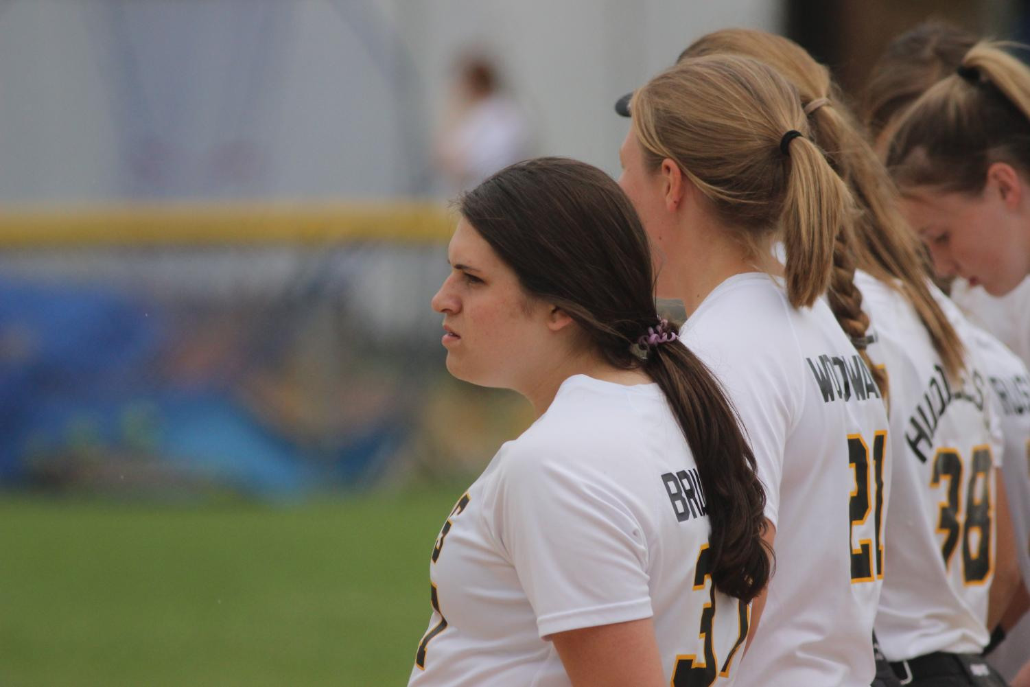 The softball girls watch the opposition during warmups.