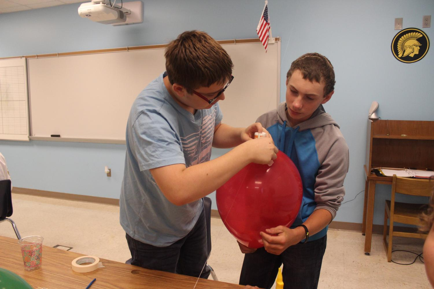 Sophomore Colin Burg and freshman Chase Vogl work on their balloon rocket. This project is just one of many that students will have to complete over the course of the year.