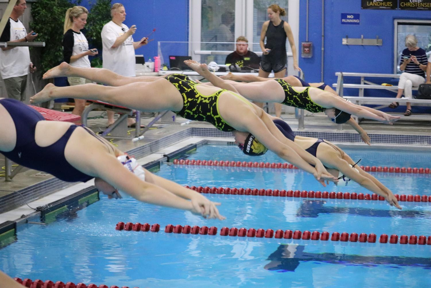 Members of the Atlantic swim team dive into the pool on Tuesday against Lewis Central. Practices and home competitions are held at the Nishna Valley YMCA.