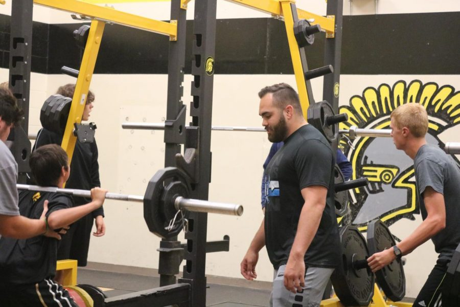 Weights teacher Connor Larson spots students during their workouts. Larson is a first-year teacher.