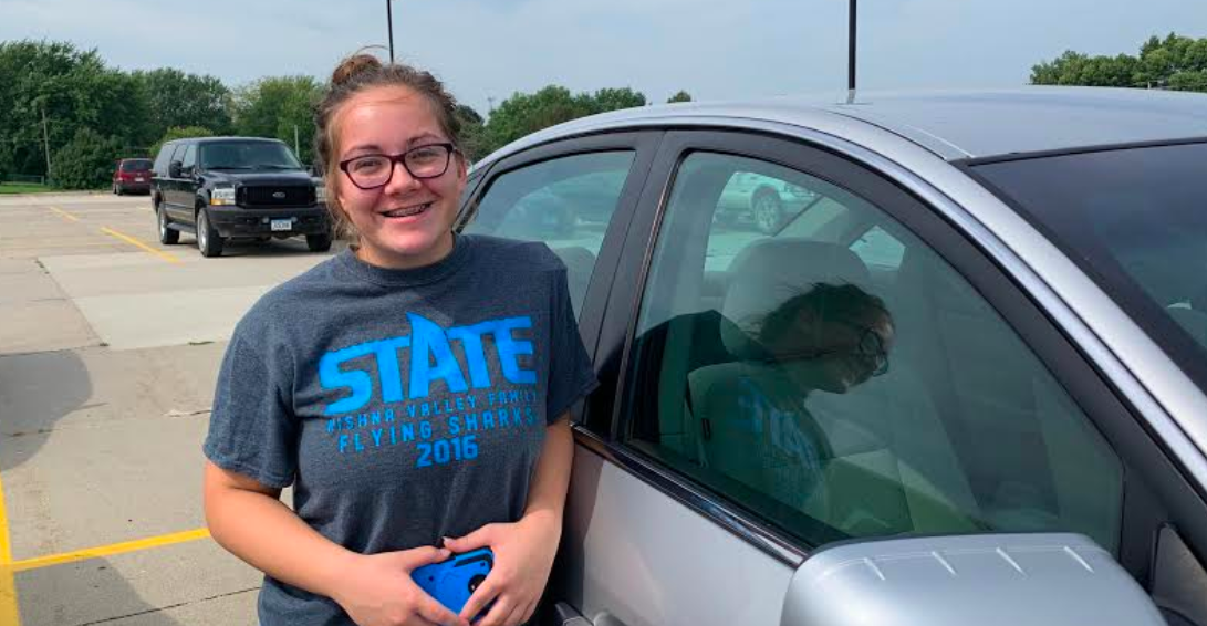Junior Dazia Sorensen stands by car in the high school parking lot. She bought her car by herself when she first turned 16. Sorensen makes all the payments on her car, with the occasional help from her parents.