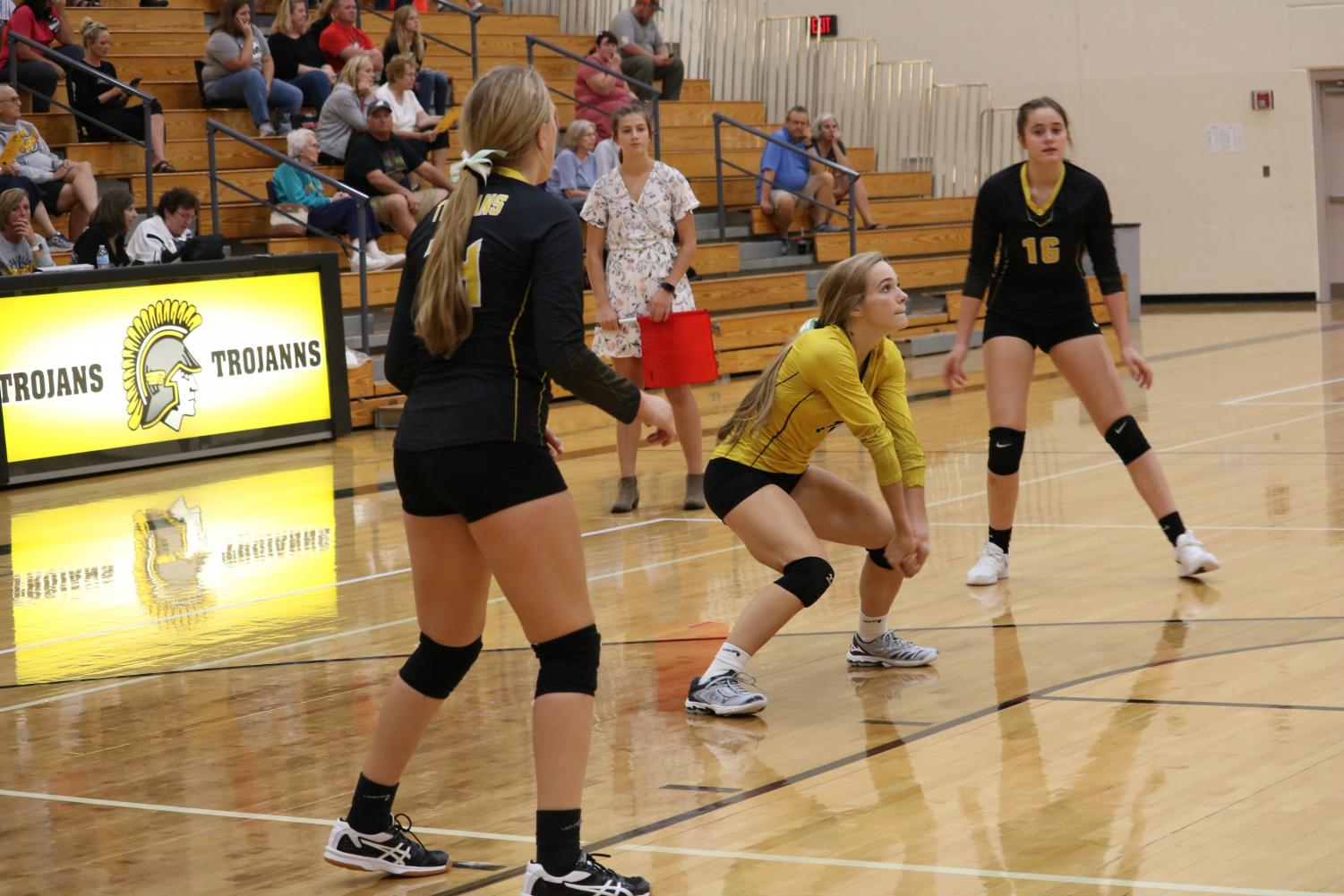 Junior Caroline Pellett digs the ball while fellow junior Maycie Waters and freshman Aubrey Guyer stand by. Pellett is third on the team in the dig category.