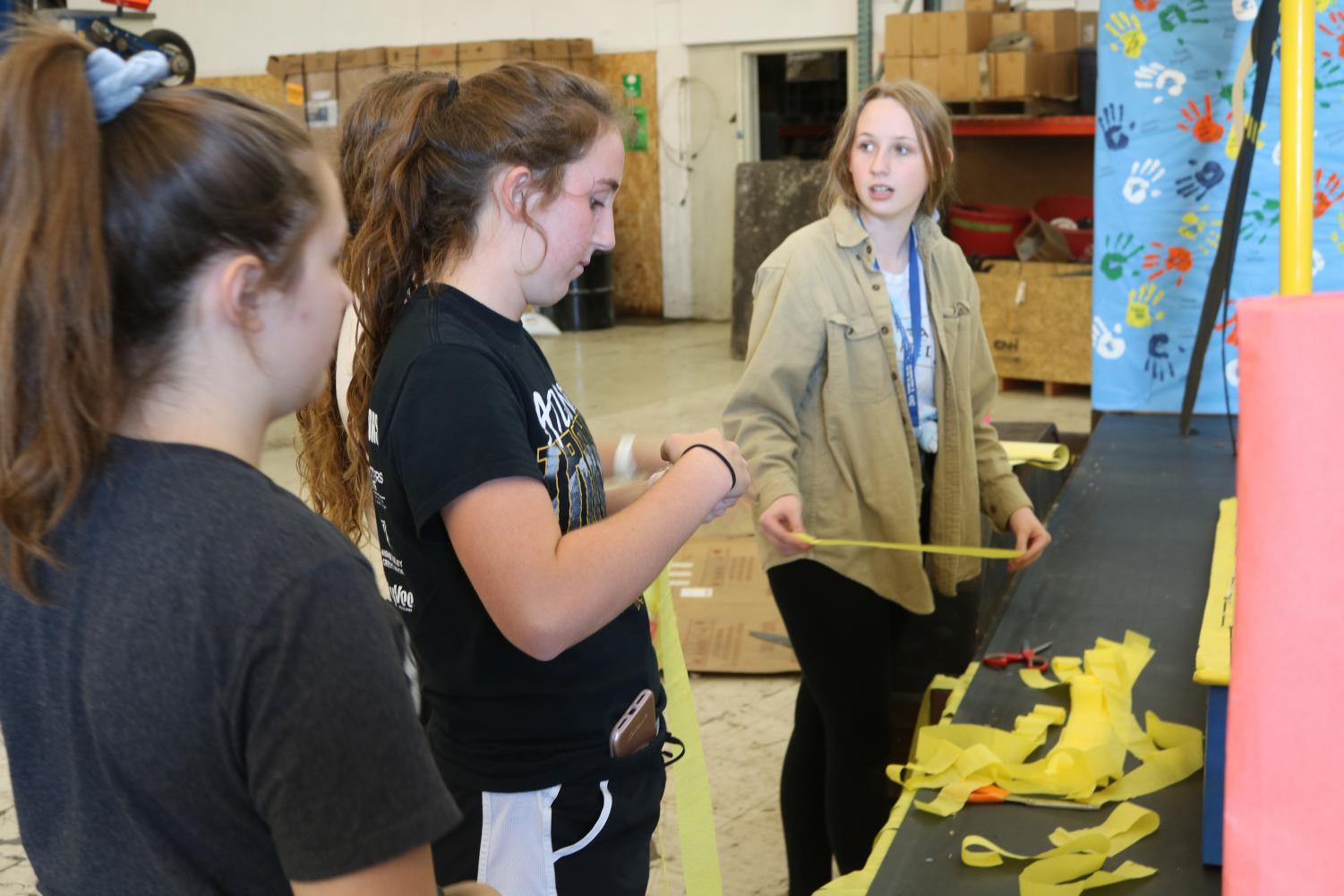 Seniors Maddy Fell, Katie Saluk, and Savannah Cameron work on their Homecoming float last year. The 2018 theme was board games.