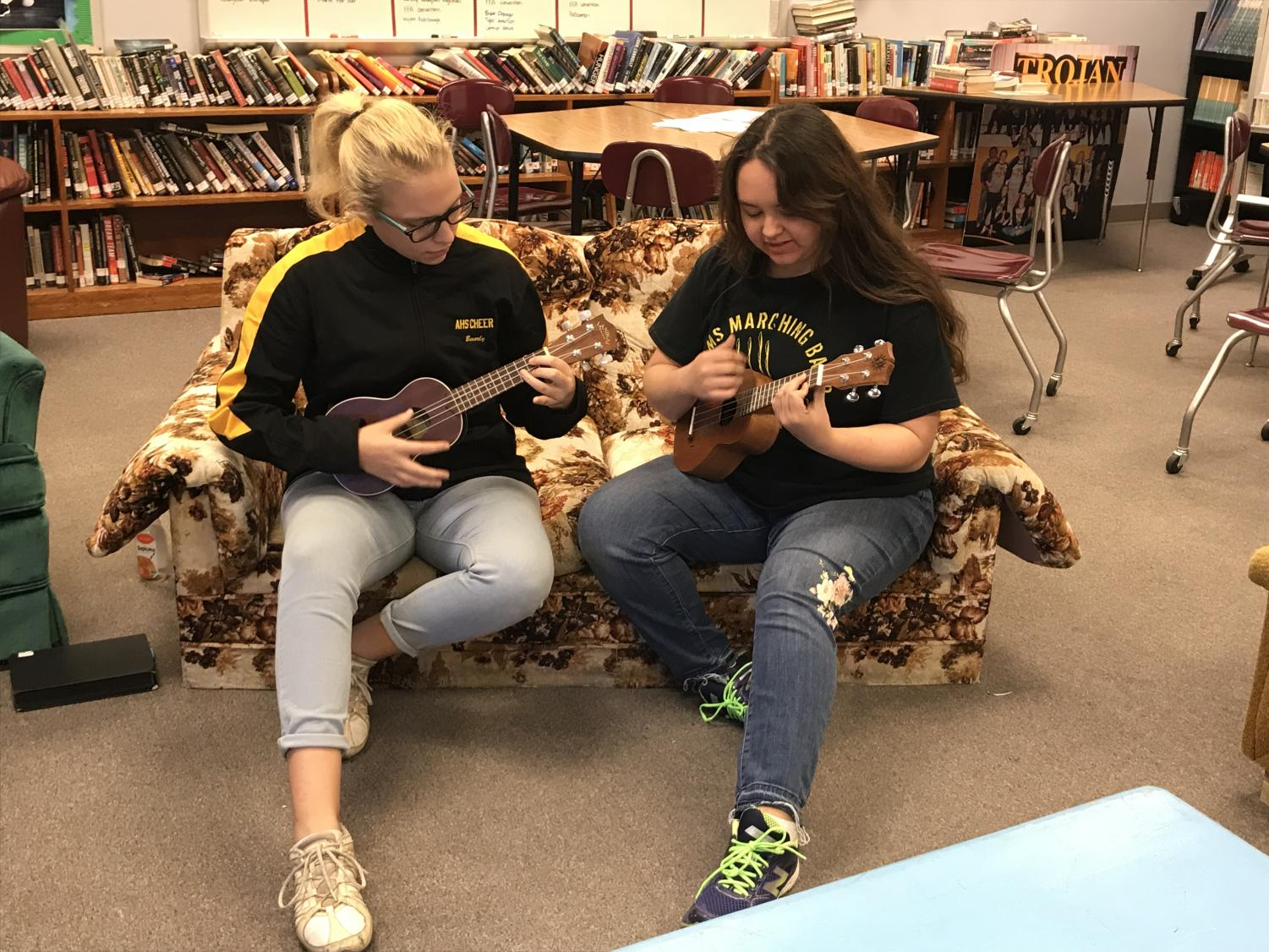 Juniors Beverly Dodson and Jasmyne Oasay-Waddell play some chords on the ukuleles in Allison Berryhill's classroom.