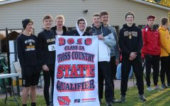The boys' cross country team hoists their state-qualifying banner up. This is the second year in a row the boys' team has made an appearance at state.