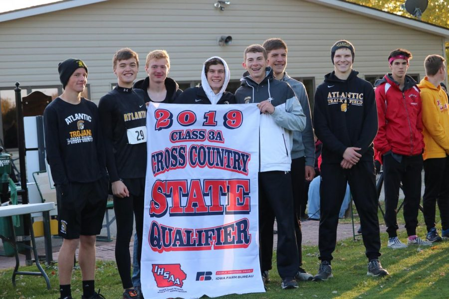 The+boys%27+cross+country+team+hoists+their+state-qualifying+banner+up.+This+is+the+second+year+in+a+row+the+boys%27+team+has+made+an+appearance+at+state.