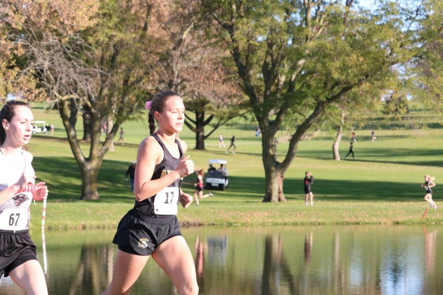 Junior Taylor McCreedy edges her opponent as she rounds a corner at the district meet. McCreedy has been the top runner for the girls' team since her freshman year.