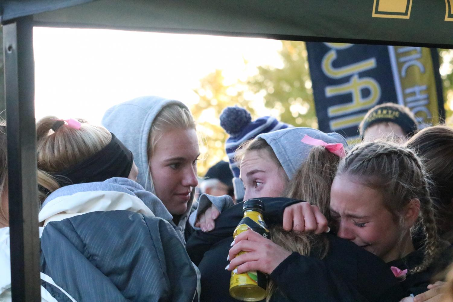 The girls cross country team comforts one another after earning fourth place at districts. Atlantic was 17 points behind the third place team, ADM.