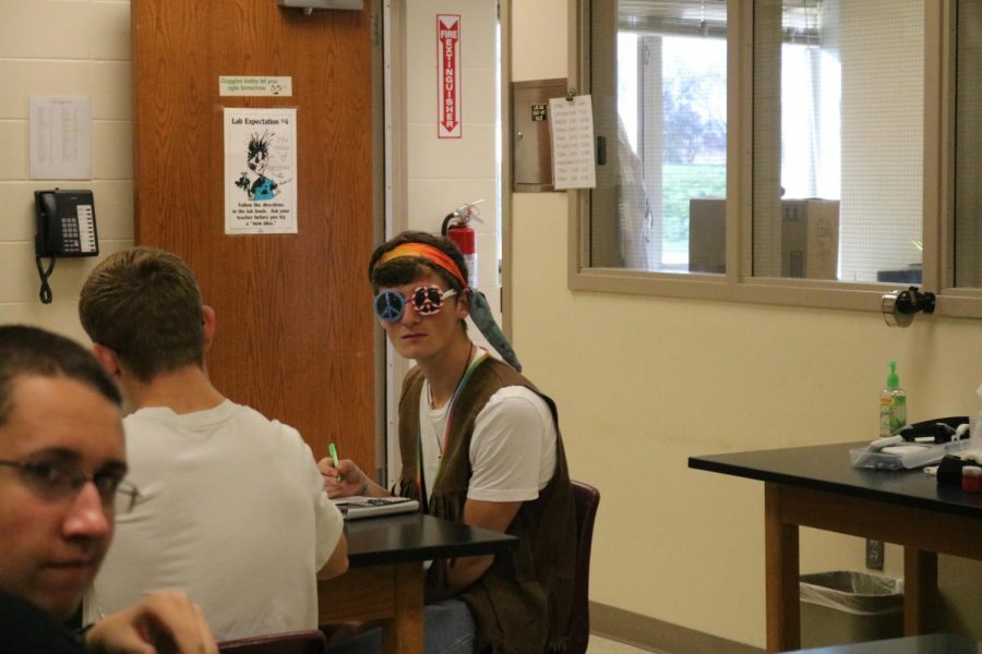 DRESSING+AS+DECADES+--+Senior+Zachary+McKay+glances+up+from+his+work+during+physics+class.+%E2%80%9CMy+family+does+a+costume+theme+every+year+and+this+year+we+voted+on+decades%2C%E2%80%9D+McKay+said.+He+choose+to+dress+from+the+sixties.+%E2%80%9CI+like+Halloween+a+lot+because+fall+is+my+favorite+time+of+year%2C%E2%80%9D+McKay+said.+