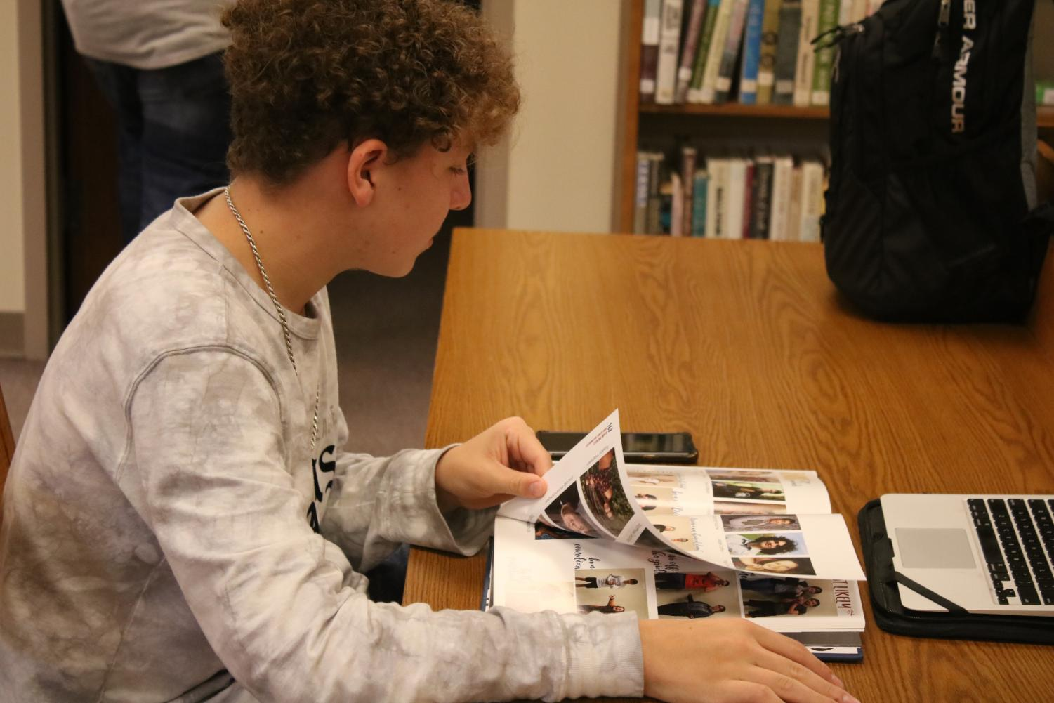 Junior Jarrit Smith scopes out the 2018-19 Javelin. The Yearbook Distribution event was held in the ICN room.