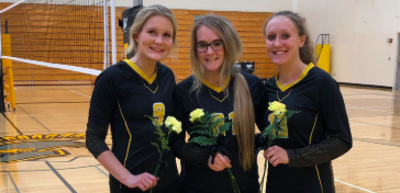 Chloe Davis, Emma Templeton, and Kenzie Waters pose with their roses on Senior Night. The three girls were involved in volleyball all four years of high school.
