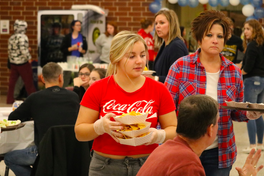 Sophomore+Kenzie+Hoffman+serves+plates+of+chips+at+the+Taco+Night+fundraiser.+All+students+who+participated+took+tickets%2C+made+food%2C+or+served+those+attending.