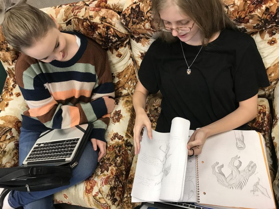 Junior Ariel Clark shows her drawings to her friend, Shayla Luke. Clark found a love with drawing when she was ten years old.