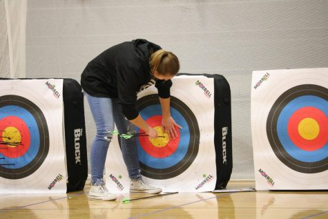 Freshman Halle Copeland collects her arrows during the bullseye event. Copeland finished first amongst the Trojan girls in the bullseye competition.