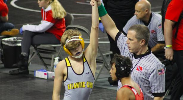 Sophomore Ethan Follman raises his arm in triumph after a win. Follman wrestles at 120 pounds.