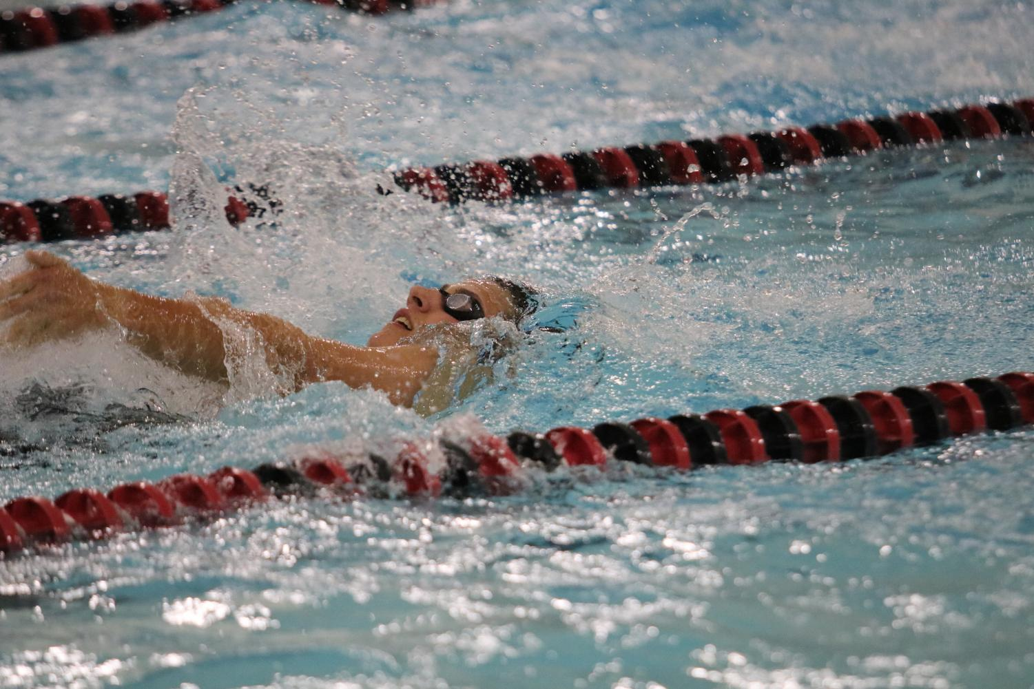 Senior Cole Sampson does the backstroke at a home meet. On Monday, Sampson was a part of the two winning relay teams.