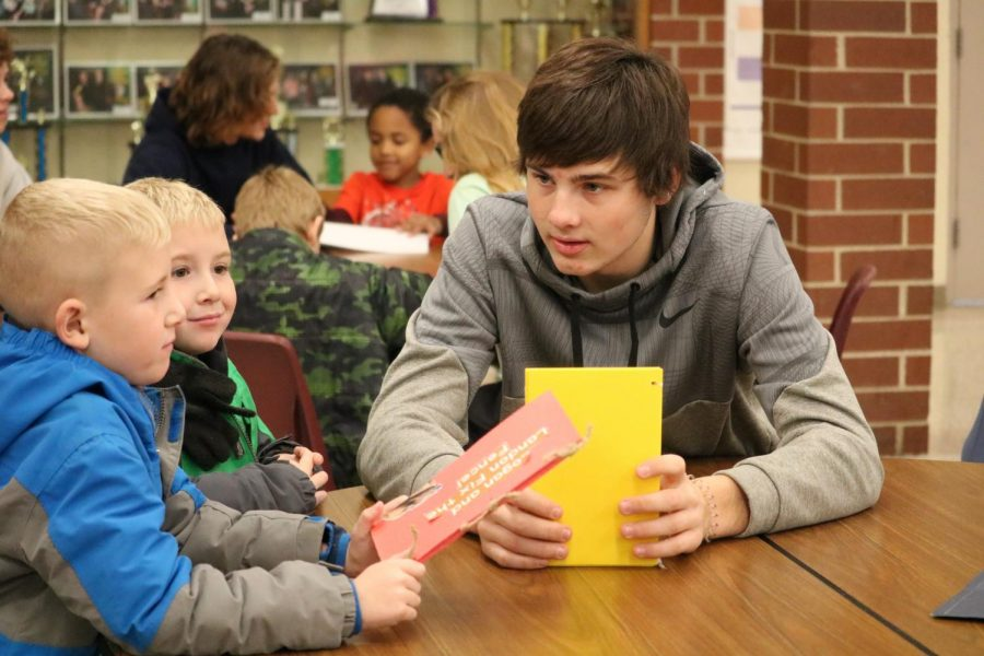 Junior Garrett Reynolds shares his children's book with two first graders. Reynolds is involved in a variety of sports.