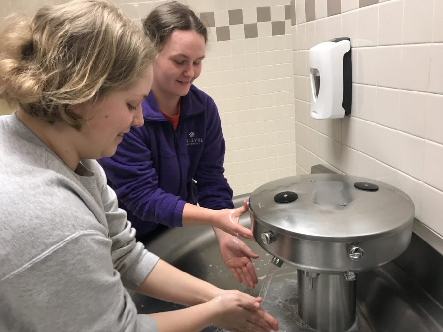 Junior Molly McFadden and sophomore Lexie Trotter scrub their hands at the sink. Twenty seconds is all that is required to get rid of germs.
