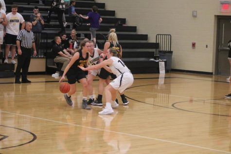 Senior Corri Pelzer sets a screen for senior Kenzie Waters. Both girls have played basketball all four years of high school.