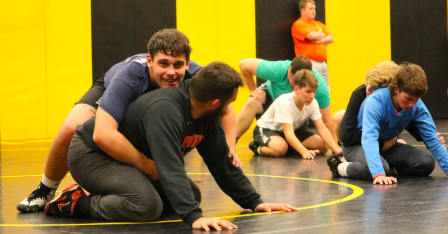 Senior Cale Roller practices his moves on assistant coach Connor Larson during practice. Roller has participated in wrestling throughout high school and has developed many skills.