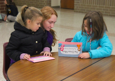 Junior Kennedy Goergen shows two elementary students the book she wrote for her English 3 class. Goergen volunteers at Washington Elementary everyday.