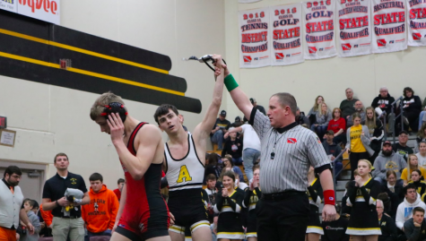 Senior Aybren Moore raises his arm in triumph. Moore qualified for State in the 113 pound weight class.