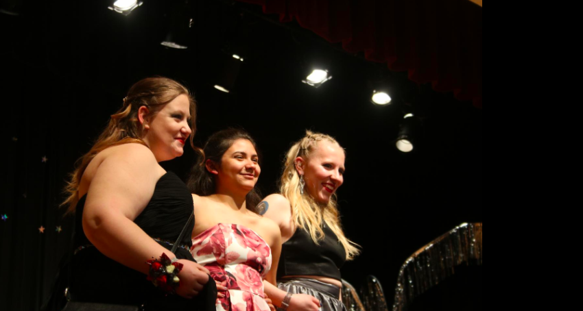 AHS alumns Hannah Anstey, Emily Gonzalez, and Summer Petty show off their dresses at Grand March.