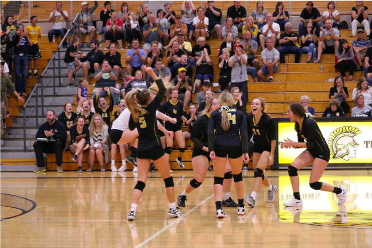 The Trojans celebrate a point together from their game in Harlan last Tuesday. They won their match against Clarinda, 3-2.