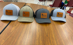 Senior Gunner Kirchhoff shows off some of Shroom Crew Outdoors' merchandise. Selling hats is one way for the brand to get advertisement and make money.
