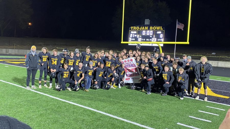 The football team poses for a picture with their state-qualifying banner. This is the first time in 18 years the Trojans qualified for state.