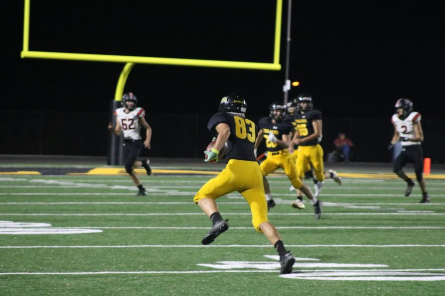 Sophomore+Jayden+Proehl+runs+the+ball.+This+was+the+Trojans%27+first+varsity+game+in+the+new+Trojan+Bowl.
