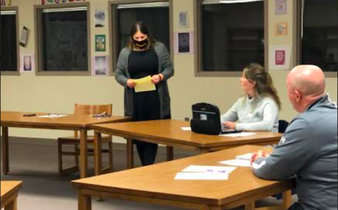 School Board member Laura McLean reads a petition signed by AHS teachers at the last board meeting. McLean was asked questions by Intro to Journalism students during their press conference.