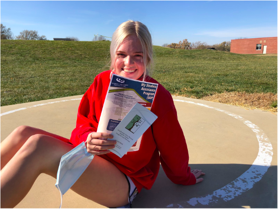 Sophomore Claire Wiederstein holds Student Assistant Program pamphlets provided by the school. Wiederstein encourages those struggling with mental health to