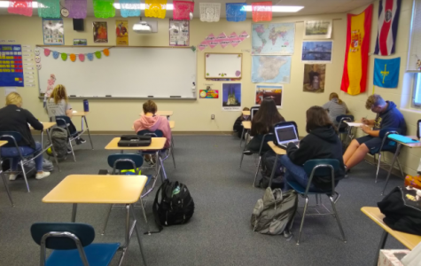 Students finish up a quiz in Trisha Niceswanger's second-period Spanish 1 class. The desks in Niceswanger's classroom are standard for most of the school and require students to look down at what they're doing. This can contribute to neck pain.