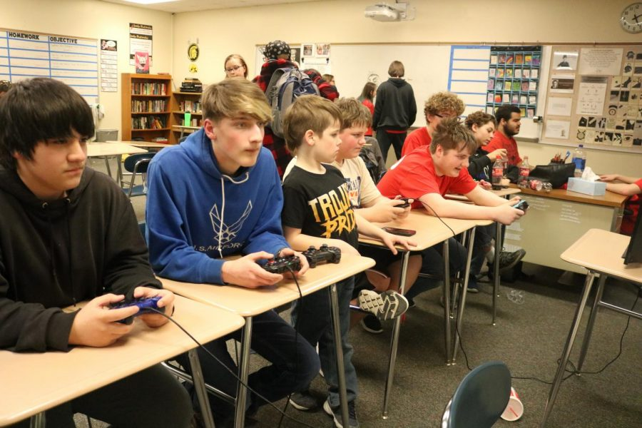 Students from game club huddle around to play video games. Benefits of playing video games include healthy brain stimulation, development of problem solving skills, and stress relief.