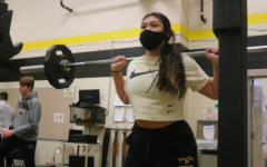 Eleanor Greving back squats to build leg muscle. Mr. Larson wrote suggested lifts on the class whiteboard. Back squat and bench press were the most common lifts this period.