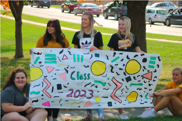 Sophomore Charlotte Saluk holds up the sophomore's homecoming poster with some of her friends.