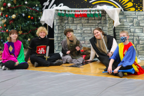 Sophomores Kylie Pulido, Cater Pellett, Reece DeArment, Charolette Saluk, and Micaiah Anderson sit around a fake fireplace while a Christmas tree twinkles in the background.  Pulido and Anderson played Jesters for the Madrigal.