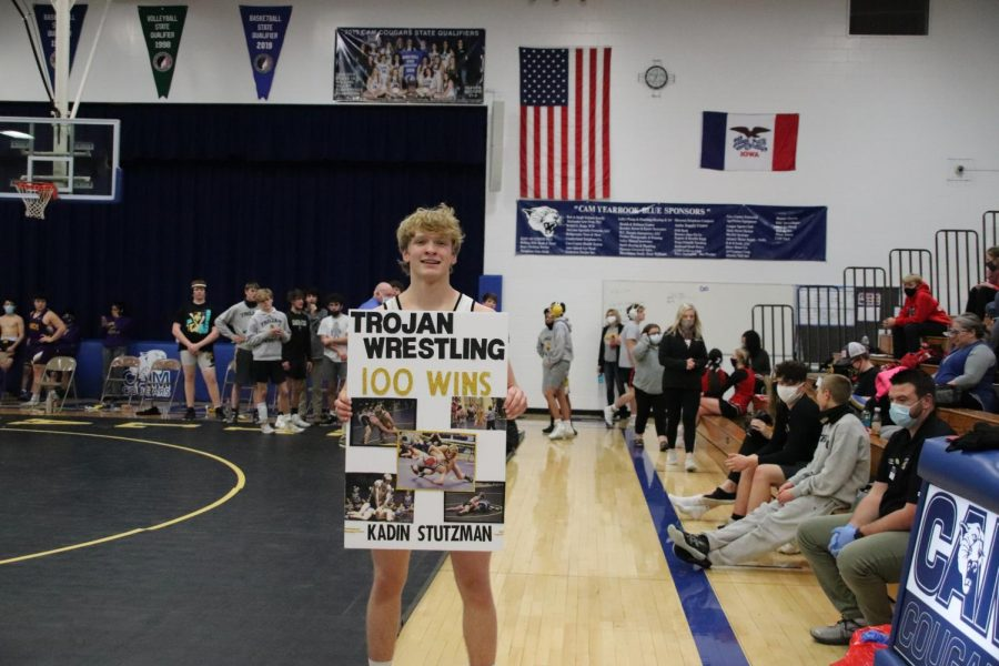 Junior Kadin Stutzman reaves a poster and treats after joining the 100 Win Club. Stutzman received his 100th win poster at a dual in CAM.