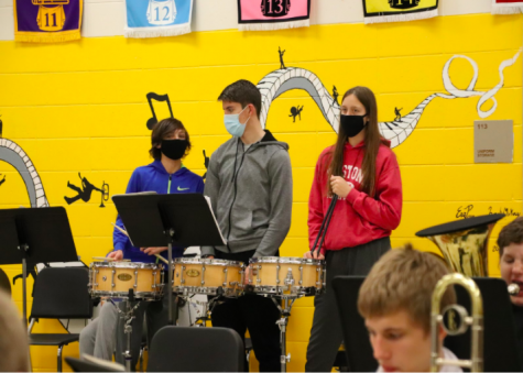 CHITTER CHATTER -  Three students take a break from the drums to talk a bit during band practice. Band students often discuss music or ask what notes they should be playing to make their music better. Talking about music and asking questions allows them to improve.