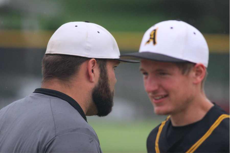 Baseball coach Joe Brummer speaks with graduate Nathan Behrends at a baseball game.