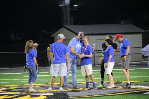 Steele McLaren and his family present the check to the Shenandoah athletic director. All the fundraisers made over $4,500.