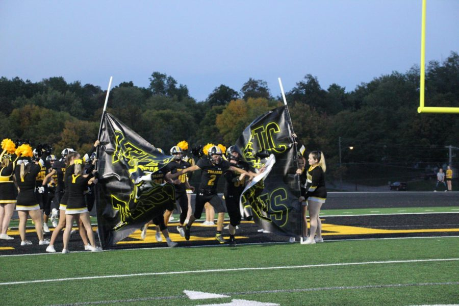 AIR TIME-  The varsity football team runs through the banner to get hype for the upcoming game. The score ended up being 42-6.